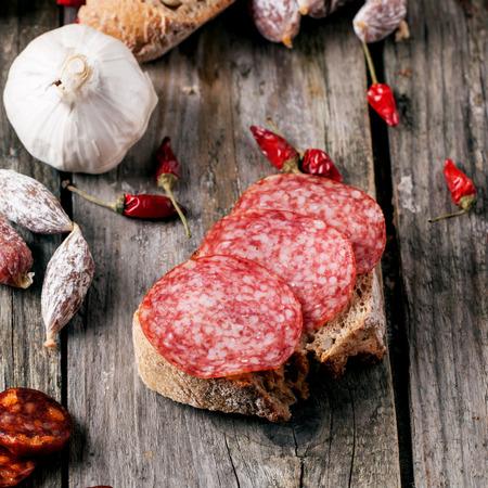 comiendo pan: Sandwich con salami slised servido con otras salchichas, pan, ajo y chiles rojos en la tabla de madera. cuadrado de imagen con enfoque selectivo