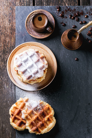 cezve: White plate with homemade belgian waffles with sugar powder, ceramic cup of coffee, old cezve and coffee beans.  Stock Photo