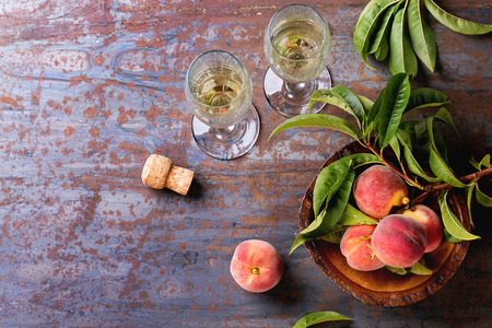 champagne glass: Peaches on branch with leaves in wooden bowl and two glass of champagne with cork over old metal background. Top view. Stock Photo