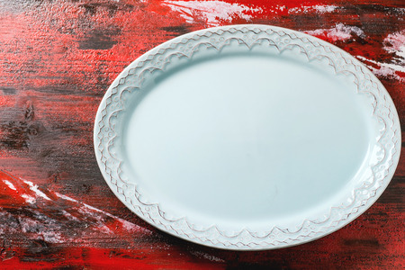 Empty blue ceramic oval plate with ornament over red-black wooden background. Top view.