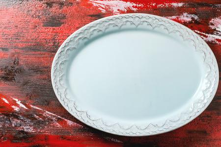 ovalo: Placa de cerámica azul vacío ovalada con ornamentos sobre fondo de madera rojo-negro. Vista superior.