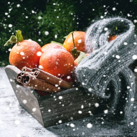the basket: Wooden basket with tangerines, cinnamon sticks and scarf over wooden background with snow and cone. Square image with selective focus