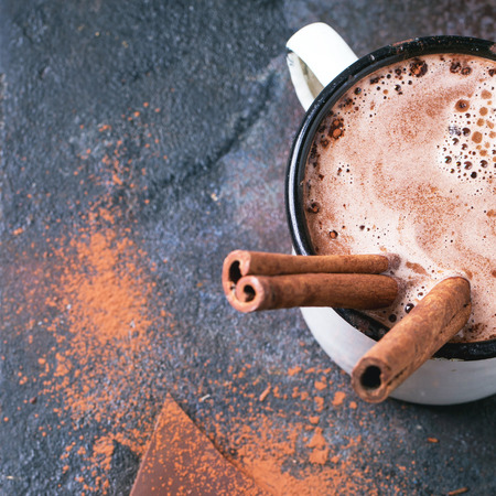 hot beverage: Vintage mug of hot chocolate with cinnamon sticks over dark background. Stock Photo