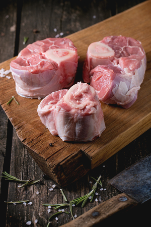 shin bone: Raw osso buco meat on wooden cutting board with vintage backsword, salt, pepper and rosemary over old wooden table. Dark rustic style. Stock Photo