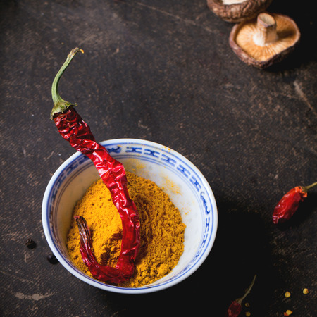 tumeric: Tumeric powder in porcelain bowl, served with shiitake mushrooms and red hot chili peppers over dark table. Square image with selective focus