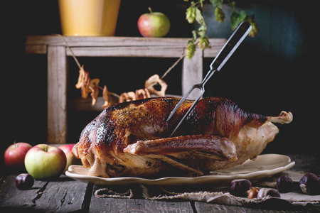 Roast stuffed goose with meat fork in on ceramic plate with ripe apples over wooden kitchen table. Dark rustic style. Stock Photo