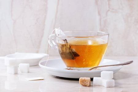 Glass cup of hot tea on saucer with sugar cubes, spoon and tea bag over white marble backgtound. Top view