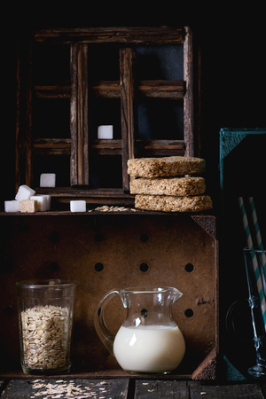 armario cocina: Glass jug of non-dairy oat milk and retro glass of oat flakes with sugar cubes and crispbread in wooden kitchen cabinet over old wooden table. Dark rustic style. Foto de archivo