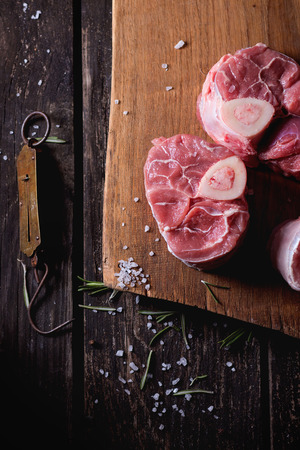 steelyard: Raw osso buco meat on wooden cutting board with vintage steelyard, salt, pepper and rosemary over old wooden table. Dark rustic style. Top view. Stock Photo
