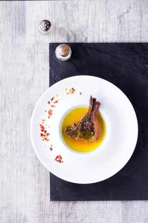 salt and pepper: White ceramic plate with well done grilled lamb chop in yellow broth with chili peppers flackes over black slate board over white wooden table. With vintage salt and pepper shakers near. Top view.