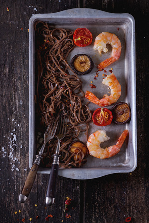 chinese food: Asian style dinner with Soba noodles, shiitake mushrooms, grilled tomatoes and shrimps in aluminum baking dish with vintage forks over old wooden background. Dark rustic style. Top view.