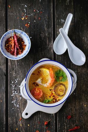 plato de comida: Cacerola blanca de cer�mica con la sopa tailandesa picante Tom Yam con leche de coco, pimienta de chile y Mariscos sobre tabla de cortar de cer�mica sobre la mesa de madera vieja. Estilo r�stico. Vista superior