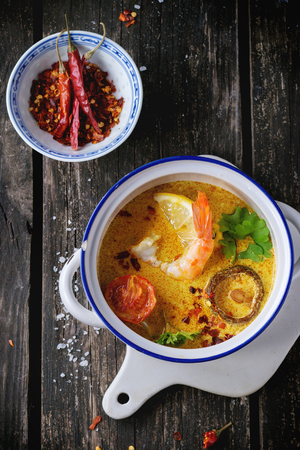 thailand food: White Ceramic pan with Spicy Thai soup Tom Yam with Coconut milk, Chili pepper and Seafood on ceramic cutting board over old wooden table. Rustic style. Top view