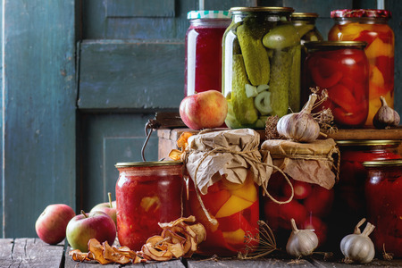 glass jars: Collection set of many homemade glass jars with preserved food (cucumbers, tomatoes, peppers), with garlic and fresh and dried apples. Over old wooden table. Dark rustic style