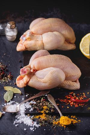 mini farm: Two Raw mini Chicken with sea salt and different spices over black slate board Stock Photo