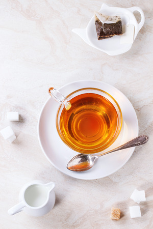 Glass cup of hot tea on saucer with sugar cubes, jug of milk and tea bag over white marble backgtound. Top view