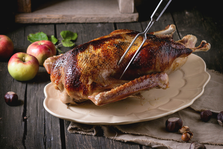 Roast stuffed goose with meat fork in on ceramic plate with ripe apples over wooden kitchen table. Dark rustic style. Archivio Fotografico