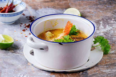 thai chili pepper: White Ceramic pan with Spicy Thai soup Tom Yam with Coconut milk, Chili pepper and Seafood over gray stone background.