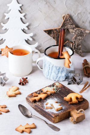 gingerbread cookies: Shortbread Christmas cookies for cups, two cups of hot tea and sugar powder over table with white tablecloth with Christmas decor at background. Shapes as Christmas tree, stars and Santa Claus Hat Stock Photo