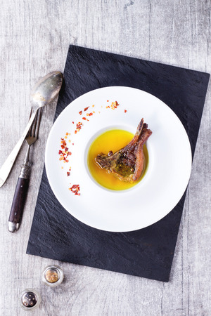 lamb chop: White ceramic plate with well done grilled lamb chop in yellow broth with chili peppers flackes over black slate board over white wooden table. With vintage spoon and fork near. Top view.