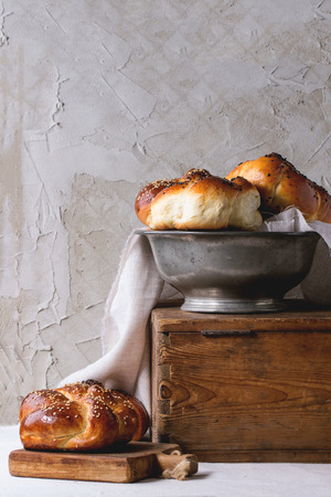 Heap of sweet round sabbath challah bread with white and black sesame seeds in vintage metal bowl on wooden chest and on small cutting board over white table with plastered wall at background.