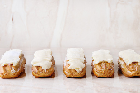 sugar powder: Eclairs with white butter cream and sugar powder over white marble surface. Outside view