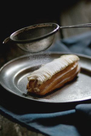 sugar powder: Single Eclair with white butter cream in vintage metal plate with Sifting sugar powder. Dark rustic style. Day light. Outside view