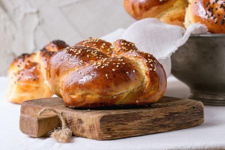 甘い丸い背景に漆喰の壁と白いテーブルの上の小さなまな板の上の白と黒胡麻と安息日カラ パンのヒープ。