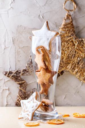 galletas de navidad: Estrella de la Navidad acristalada da forma a las galletas en vidrio con la decoración de Navidad y rodajas de naranja seca sobre tabla de madera blanca. Con enlucido de la pared como fondo. Vista desde fuera