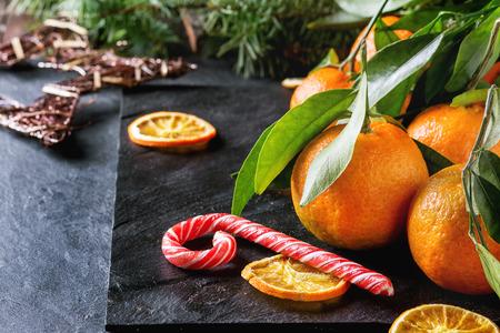 frutas secas: Mandarinas con las hojas en la decoraci�n de Navidad con el �rbol de Navidad, naranja seca y dulces sobre la superficie de la pizarra negro. Vista lateral.