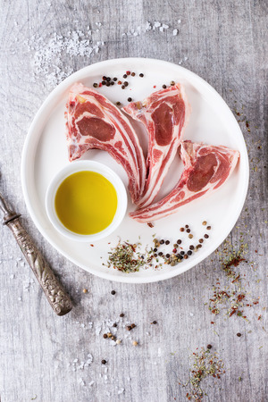lamb meat: Raw lamb chops with salt, pepper, dry herbs and bowl of olive oil on white ceramic plate over white wooden table. Meat fork near. Top view.