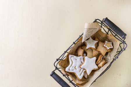 oude krant: Glazed Christmas cookies as stars shapes in basket with old newspaper over white wooden surface. With copy space at left Stockfoto