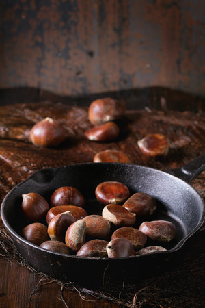 cast iron: Uncooked edible chestnuts in cast iron skillet over wooden table