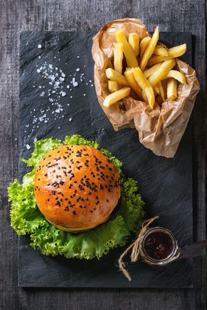Fresh homemade hamburger with black sesame seeds and french fries potatoes in backing paper, served with ketchup sauce in glass jar and sea salt on black slate board over wooden surface. Top view