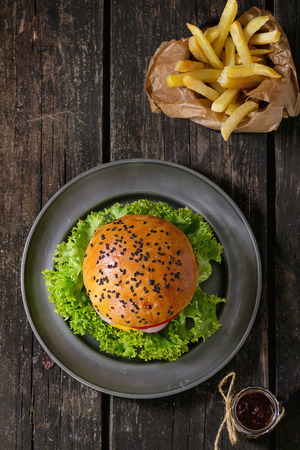 Fresh homemade burger with black sesame seeds in metal plate and fried potatoes in backing paper, served with ketchup sauce in glass jar over old wooden surface. Dark Rustic style. Top view 版權商用圖片