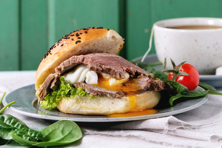 roast meat: Close up of homemade sandwich with baked meat and soft-boiled egg liquid yolk, spinach salad, cherry tomatoes and cup of hot pocket tea over white wooden table with turquoise wall at background.