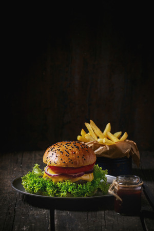 Fresh homemade hamburger with black sesame seeds in old metal plate with fried potatoes, served with ketchup sauce in glass jar over old wooden table with dark background. Dark rustic style. Foto de archivo
