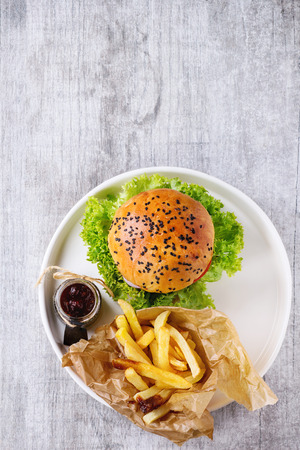 Fresh homemade burger with black sesame seeds in white plate with fried potatoes, served with ketchup sauce in glass jar over gray wooden surface. Top view