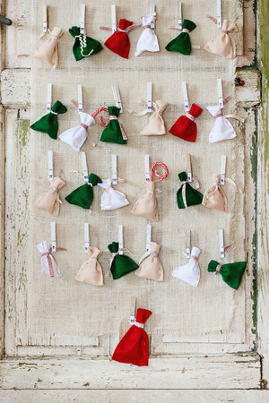 Handmade Advent calendar with small colorful pouches on wooden pins over white wooden door