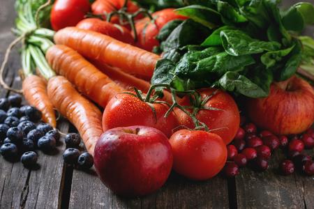 Sortiment von frischen Früchten, Gemüse und Beeren Karotten, Spinat, Tomaten, rote Äpfel, Heidelbeeren und Preiselbeeren über alten Holztisch.