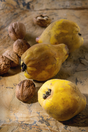 quinces: Three whole juicy quinces with whole and split walnuts over natural brown stone surface in sunlight. Stock Photo