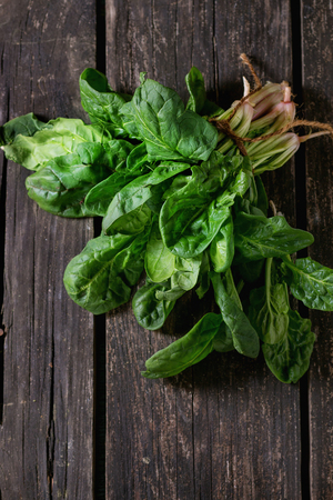 Bunch of fresh spinach with roots over old wooden surface. Dark rustic style. Top view