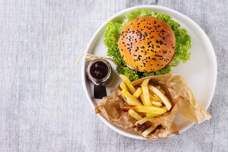 hamburguesa casera fresca con semillas de sésamo negro en la placa blanca con las patatas fritas de patatas, servido con salsa de tomate en frasco de vidrio sobre la superficie de madera de color gris. Vista superior
