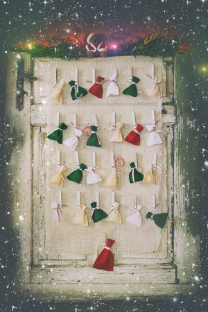 Handmade Advent calendar with small colorful pouches on wooden pins over white wooden door. With retro filter effect and falling snow Stock Photo