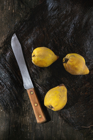 quinces: Three whole juicy quinces with vintage knife over black wooden table in sunlight. Dark rustic style. Top view