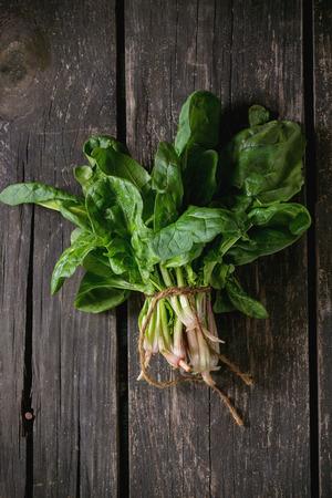 新鮮菠菜超過舊的木製表面根的一群。黑暗的鄉村風格。頂視圖 版權商用圖片