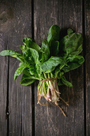 fresh spinach: Bunch of fresh spinach with roots over old wooden surface. Dark rustic style. Top view