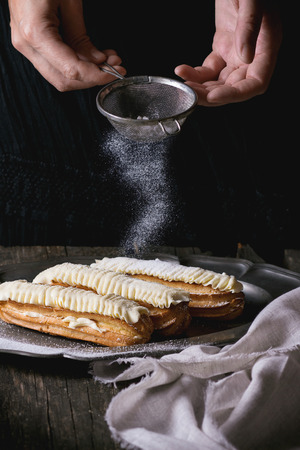 sugar powder: Eclairs with white butter cream in vintage metal plate with Sifting sugar powder from womans hands. Dark rustic style. Day light. Outside view Stock Photo
