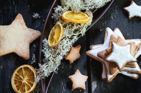 baking christmas cookies: Christmas glazed star shapes cookies with Christmas tree, moss and dry sliced orange in ceramic plate over red wooden table. Dark rustic style, day light. Top view