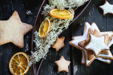 galletas de navidad: Estrella de la Navidad acristalada da forma a las galletas con el árbol de Navidad, el musgo y las rodajas de naranja seca en placa de cerámica sobre la mesa de madera de color rojo. estilo rústico oscuro, la luz del día. Vista superior